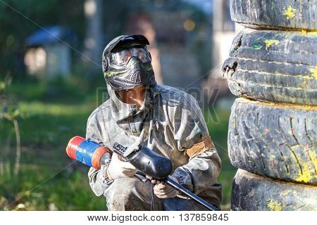 Paintball player with paint gun sitting behind fortification