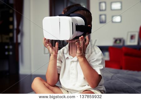 Small boy is sitting on sofa at home and watching something in virtual reality glasses