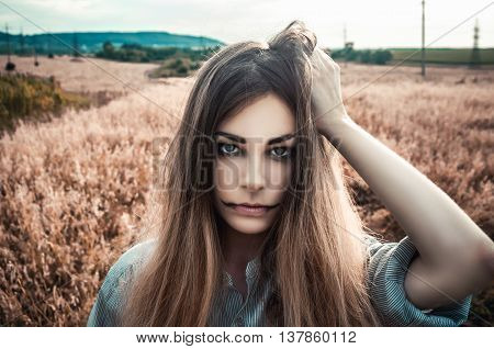 Beautiful and young girl in a man's shirt standing in the field. Halloween girl zombie. Halloween makeup. Fog. shirt for the girl. Nature. Wind inflates hair.