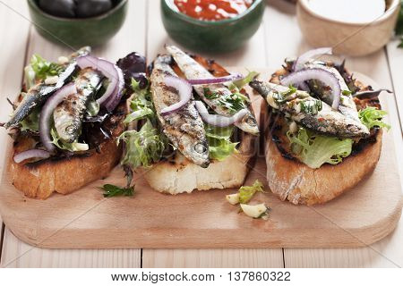 Italian crostini sandwich with grilled sardine fish, onion and lettuce
