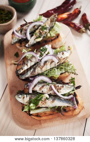 Italian crostini sandwich with grilled sardine fish, lettuce and onion