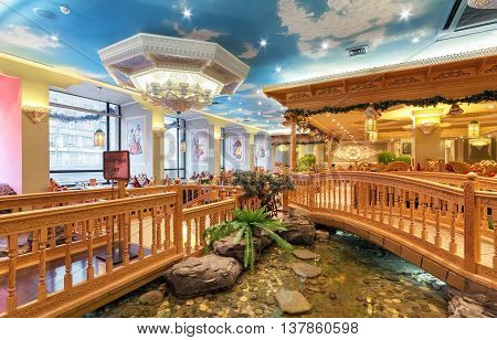 MOSCOW/RUSSIA - DECEMBER 2014. The interior of the deluxe restaurant of Uzbek cuisine - Babay Club in an oriental style. Pond and wooden bridge in the restaurant