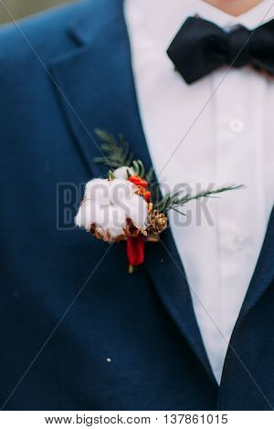 Groom's creative boutonniere on the suit close up.