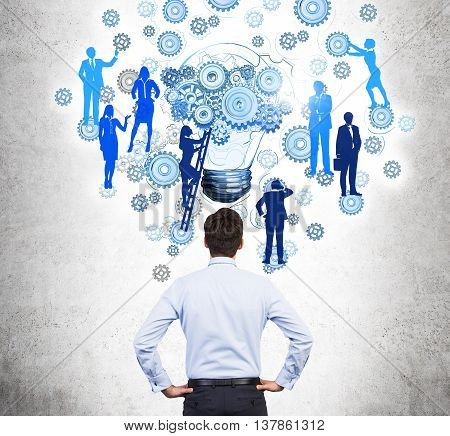 Teamwork concept with businessman looking at abstract drawing of gears lightbulb and people silhouettes on ladder. Concrete wall background. Back view