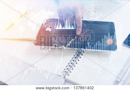 Closeup of male hand using tablet with abstract business charts and graphs on office desktop with various items. Toned image