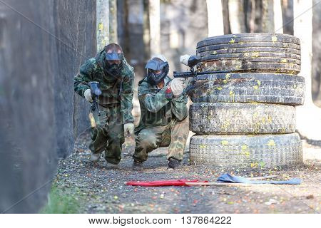 Two friends in extreme paintball training with capturing flags.