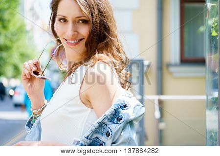 Young smiling brunette woman in profile takes off denim jacket and looking at camera