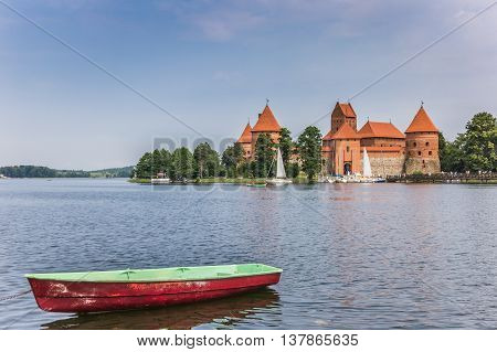 Trakai castle and a red and green boat in lake Galve
