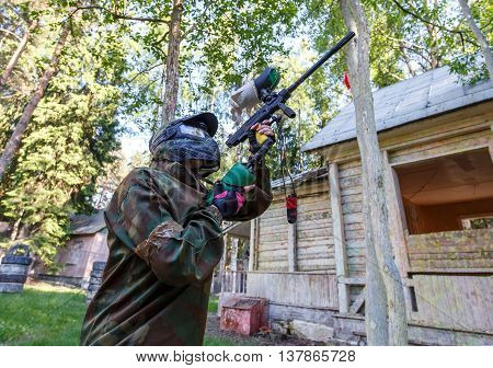 Cool young woman with paint gun playing paintball game