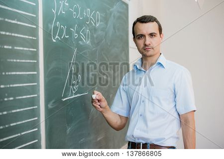 Young male teacher holding chalk writing on chalkboard in classroom.