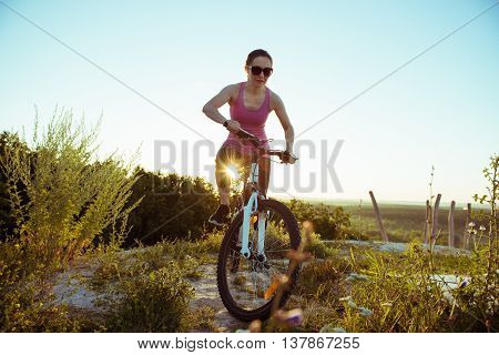 a beautiful young woman rides a bike on the nature day