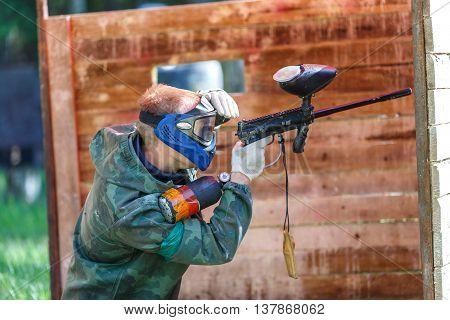 Paintball player in blue helmet shooting from paint gun