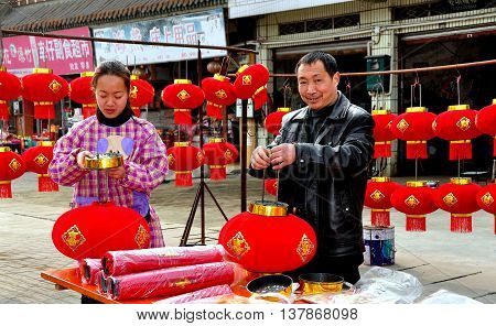 Jun Le China - February 3 2013:  Husband and wife preparing to display red fabric Chinese Lunar New Year lanterns at their roadside stand on the town's main street