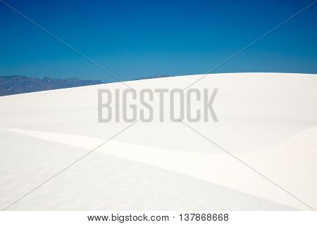 The view of a white gypsum sand dune at hiking at White Sands National Monument.