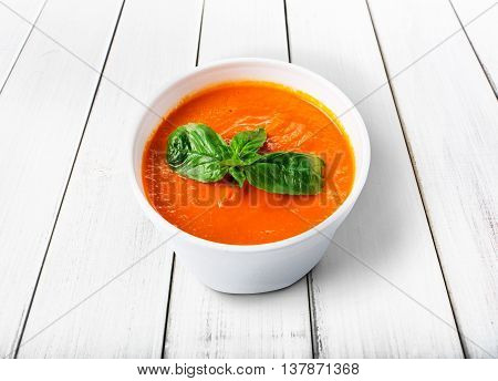 Spanish cuisine hot food delivery - tomato diet cream soup gazpacho at white wood background in white plastic plate