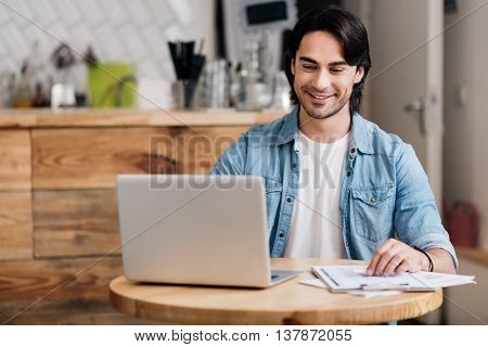 Self Employed. Smiling and cheerful young man using a laptop while being owner of business