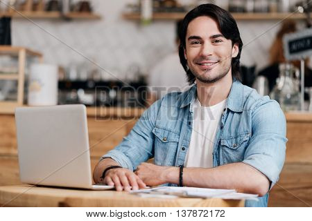 Keeping in touch. Happy and content young man using his laptop while being in a cafe and smiling at a camera