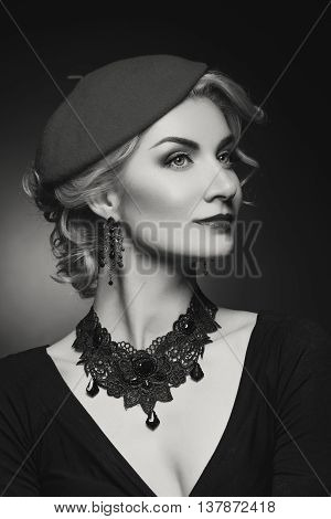 Beautiful lady in beret. Beauty portrait. Film noir retro style. Over black background. Monochrome.