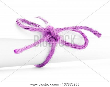 Handmade pink rope knot tied on white letter roll isolated