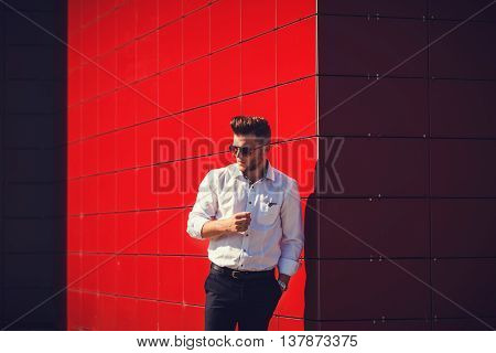 handsome man in white shirt posing on a red background