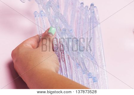 Hangers Isolated On The Pink Background. Choosing Clothes Hangers. Female Hands Closeup.