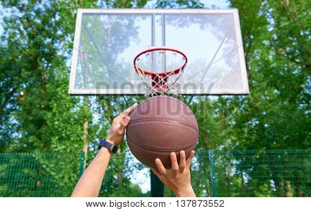 Hands throwing basketball ball into basket against green trees