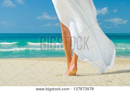 Young woman in white dress walking alone on the beach