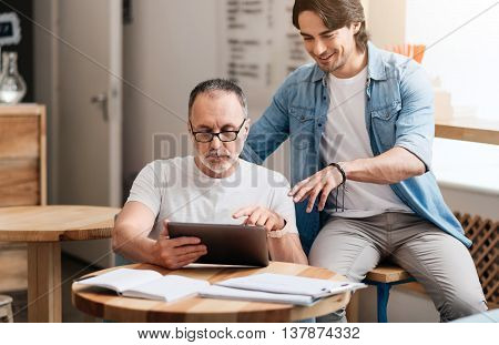 Loving son. Happy and smiling young man helping his cheerful father to use tablet being in a cafe