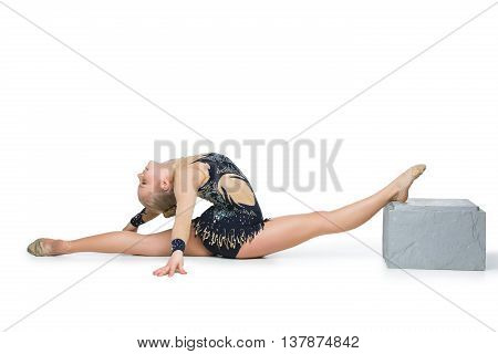 Gymnast girl in beautiful costume sitting in twine. Isolated over white background. Copy space.