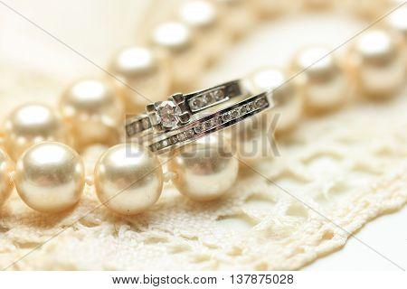 Engagement ring and wedding band with diamonds on a pearl necklace