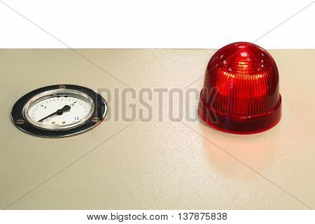 The red warning light and the instrument pointer. Beige assembled on a metal panel.