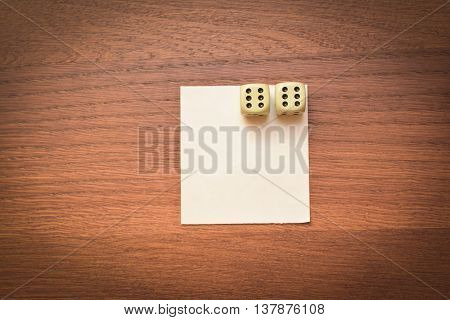 two dice and a clean sheet on a wooden table