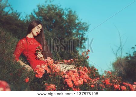 Nature sits a woman with long hair among the roses.