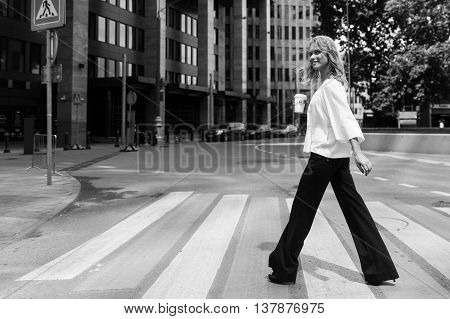 Stylish young woman crossing the road in modern quarter in the city with coffee in hand. Black and white image