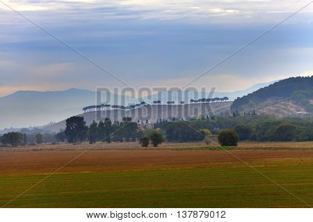 Italy. Green fields and mountains in morning fog.