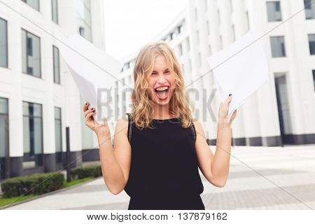 Young happy business woman with documents in hand happily shouts. Split toned photo