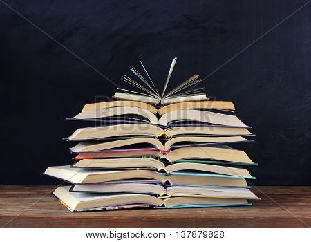 Stack of open books on the table in the background of a school blackboard. Back to school.