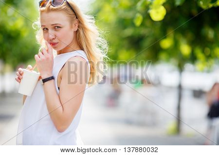 Beautiful happy woman in white blouse sipping milkshake in park