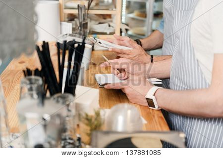Noting. Cropped image of two male cafe workers in apron making some notes