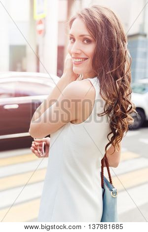 Beautiful brunette crosses the road at pedestrian crossing and looks back. Image with lens flare effect