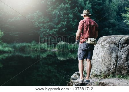 Man fishing, casting with ultralight rod standing on the rock, flare is visible in the frame