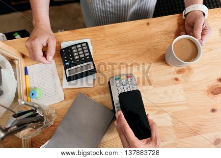 Checkout operations. Cropped image, top view of man paying with NFC technology on mobile phone being in coffeehouse