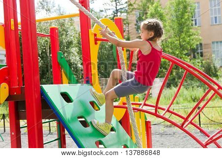 Little caucasian girl dressed in a red jersey playing on playground, climbing the wall on a rope