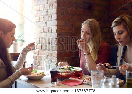 Three attractive young women friends relaxing over lunch together in a restaurant sitting at a table chatting and enjoying their food