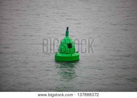 Color image of a buoy floating in water.