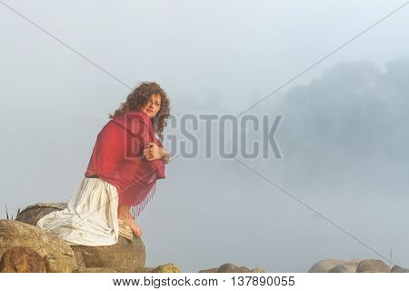 Pretty young woman sits on a stone in fog