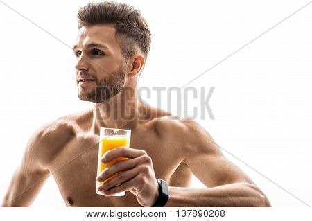 Juice is good for my healthy. Joyful fit man is holding a glass and smiling. He is standing and looking sideways with happiness. Isolated