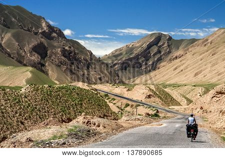 Single female cyclist on the bicycle on the remote road in Xinjang province leading to Western Tibet