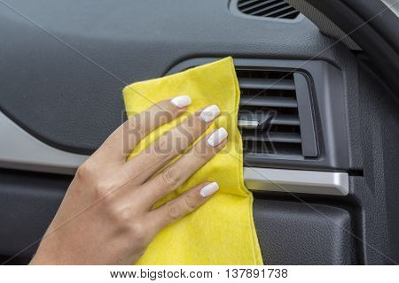 Hands girls wipe yellow cloth car interiors.