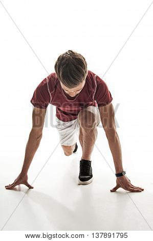 Cheerful man is ready to run. He is kneeling at start position. Sportsman is looking down with concentration. Isolated